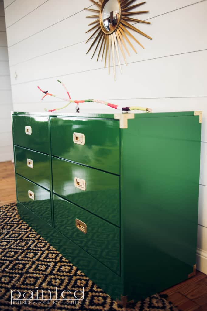 glossy green campaign dresser painted in Fine Paints of Europe Hollandlac Brilliant with brass hardware. ship lap walls. yard covered stick. sunburst mirror