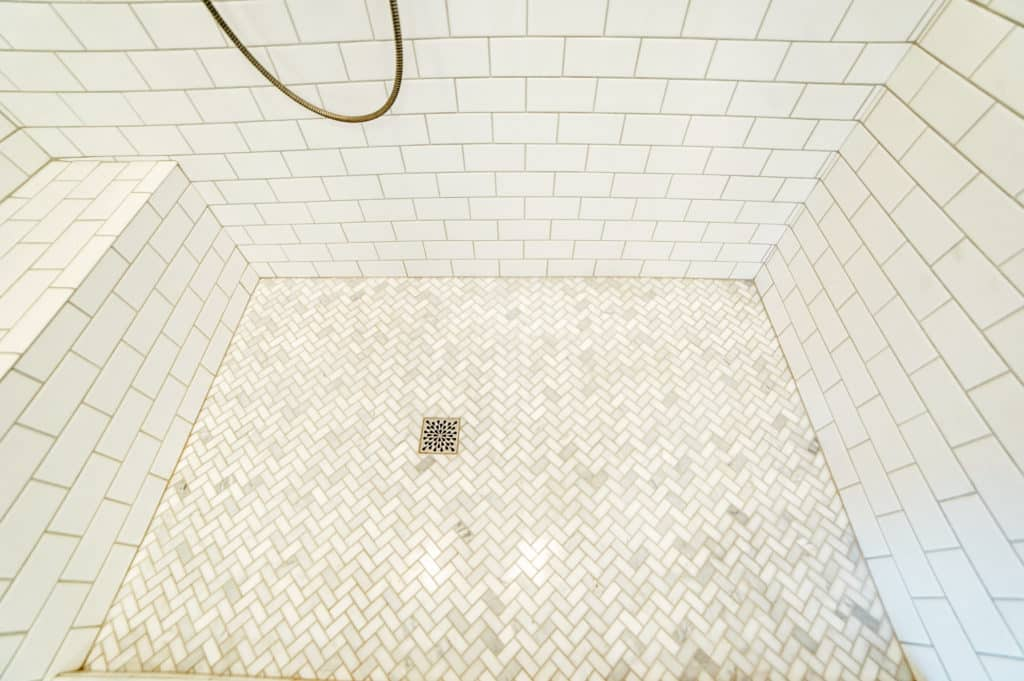 Marble herringbone tile shower floor with classic white subway tile walls.