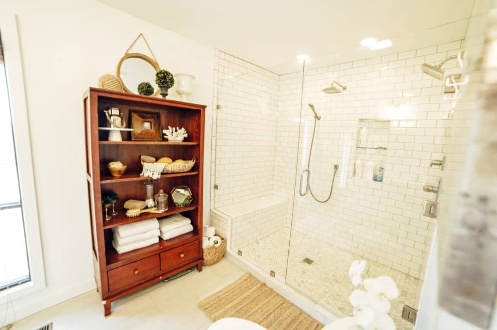 Bright and fresh master bathroom with huge walk-in shower with frameless glass doors and dual shower heads.