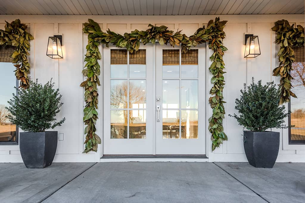 Fresh Magnolia Garland around front door and windows makes a simple, Christmas front porch!